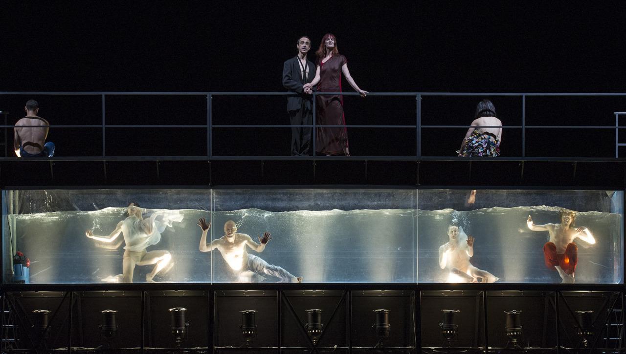 Cuando uno llega al Colón para ver una ópera barroca y se encuentra con una gran pileta llena de agua suspendida en el medio del escenario… Cuando la primera pareja se arroja a la pileta desde bordes opuestos en exacta coincidencia con el primer...