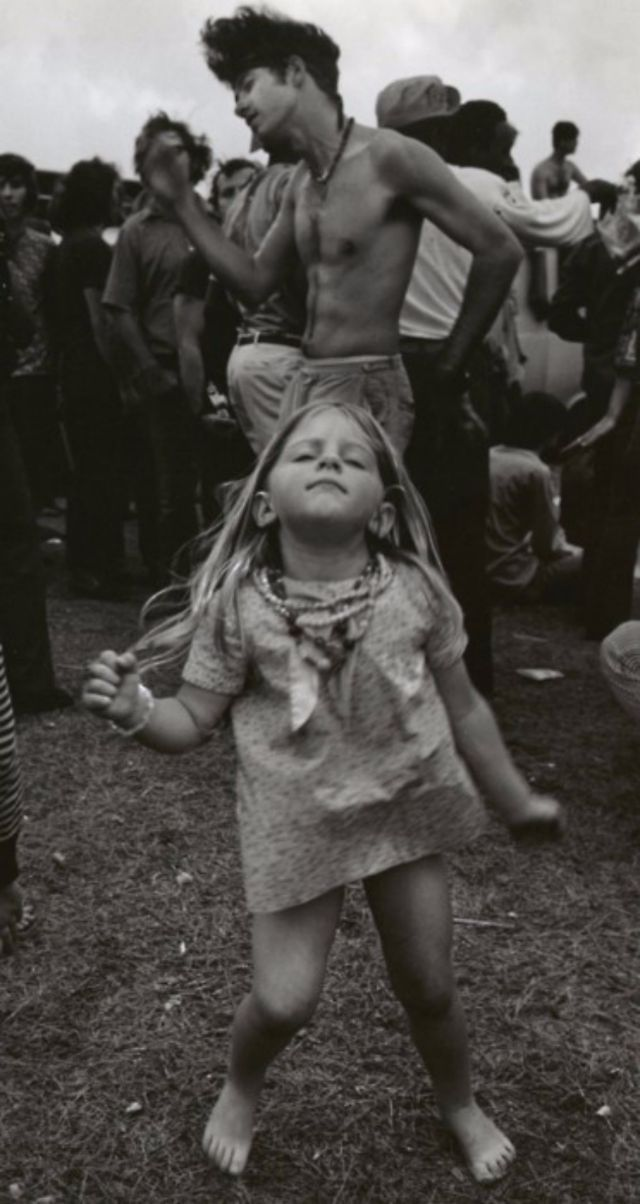 Little hippie girl going dance crazy at Woodstock, 1969.