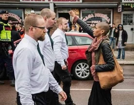 """Svezia, pugno alzato davanti al corteo di estrema destra: Tess Asplund sfida 300 neonazisti Braccio alzato e pugno chiuso: questo il gesto di Tess Asplund che ha fatto il giro del mondo. Lei, una donna 42enne di colore, che ha sfidato 300 neonazisti in uniforme durante il corteo del Movimento di resistenza nordica (Nordiska motståndsrörelsen) a Borlänge, nella Svezia centrale. """"Ho agito d'istinto. Ero così arrabbiata che sono scesa in strada e mi sono messa di fronte a loro"""", ha raccontato Asplund. La donna subito dopo il gesto è stata immediatamente sollevata di peso e fatta sgombrare dalla polizia, per far proseguire la marcia dei neonazisti."""