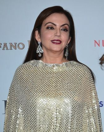 Nita Ambani standing at the podium after winning the gold in women's individual fencing competition.