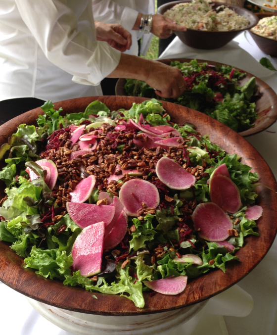 A large salad featuring fresh vegetables for a large catering event