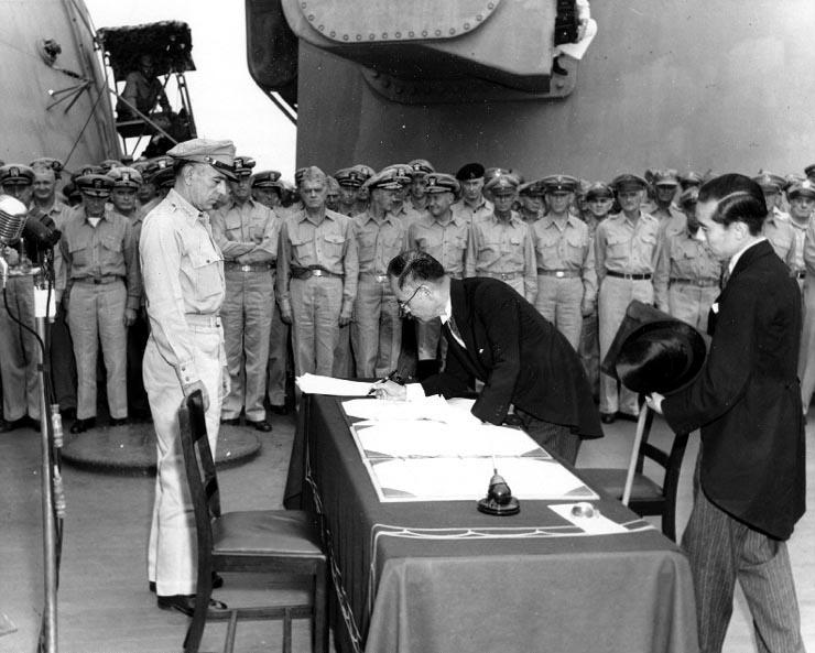1945年9月2日、USSミズーリ艦上でリチャード・サザランド中将が見守る中、降伏文書に署名する重光葵外務大臣、右随行の加瀬俊一