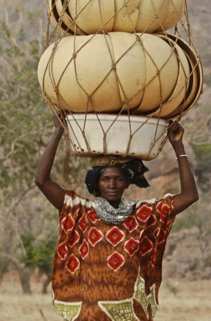 African woman carrying huge stack of bowls on her head