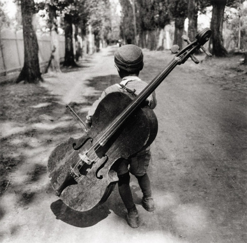 """joeinct: """"Untitled, Gypsy Boy with a Violoncello, Balaton, Hungary, Photo by Eva Besnyö, 1931 """" Write a poem about this photo."""