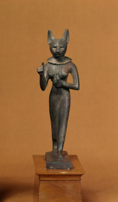 lionofchaeronea:Standing statuette (bronze with gold inlay) of the ancient Egyptian cat-goddess Bastet, holding an usekh-collar topped by a feline head and sun-disk. Artist unknown; ca. 400-250 BCE (Late Period or early Ptolemaic). Now in the Walters Art Museum, Baltimore. Photo credit: Walters Art Museum.