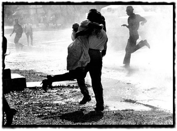 After being hit from behind and knocked down by a water hose, a woman is carried away by a fellow demonstrator, 1963.  Photo credit: Does anyone know who took this photo?