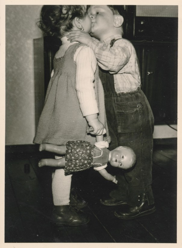 65bbce87f2 Boy kissing a girl holding a doll (unknown date). – History