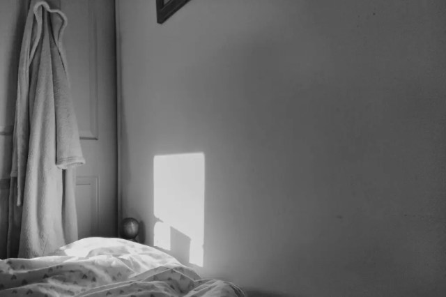 A square of light falls on a wall, alongside a dressing gown hanging from a door.