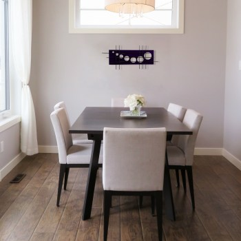 this neutral pallet dining area is accented with Holy Stix metal wall decor by 7055 Inc in an aged purple finish