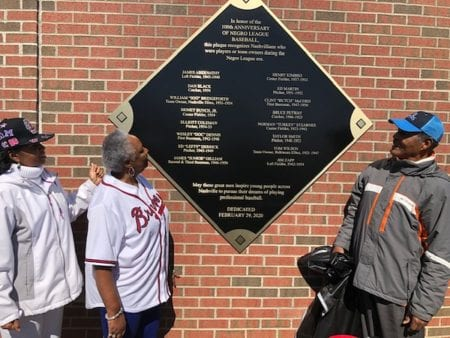 Event leaders admire the new historical plaque