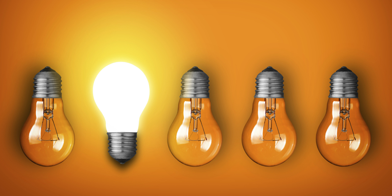 Idea concept with row of light bulbs and glowing bulb
