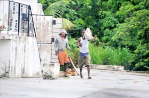 "Jamaica Observer photo with caption ""These two men dash out of an unoccupied house at 16 Millsborough Avenue in St Andrew with a bag of bottles and other missiles which they flung at a Jamaica Observer photographer."""