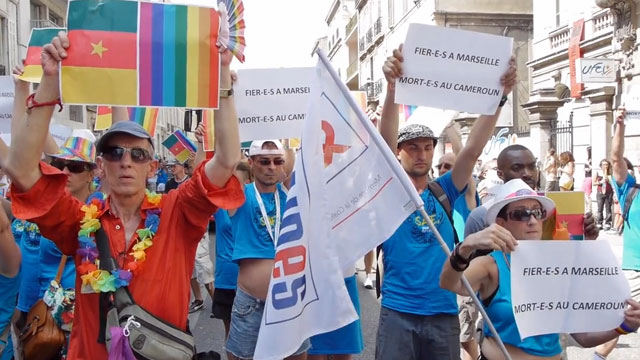 "Marseilles Pride marchers in France devote a moment of silence to Eric Lembembe last month. The signs state, ""Proud in Marseilles. Dead in Cameroon."" (Click image for video, in French.)"