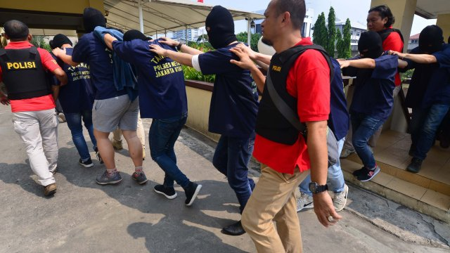 Indonesian police escort several of the 141 people arrested in the May 22 raid. (Photo courtesy of Inquirer News)
