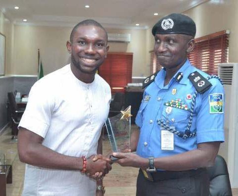 Samuel Uchenna, executive director of Levites Initiative for Freedom and Enlightenment, presents an award to Muhammad Mustafa, the police commissioner for Delta State, Nigeria. The award honors him as as an effective and friendly police officer. (Mike Daemon photo)