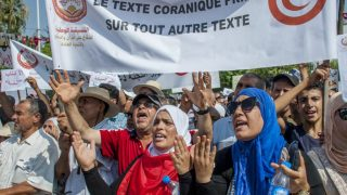 "Protesters carry a banner reading ""Quran text before any other text"" outside the Tunisian capital of Tunis on Aug. 11. (Hassene Dridi photo courtesy of the Associated Press)"