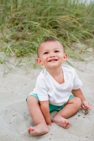 Baby smiles for picture at the beach