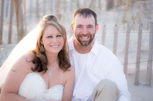 Wedding couple getting pics in front of a wooden fence