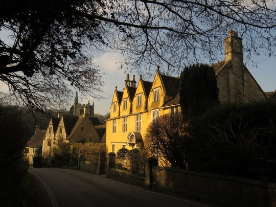 A yellow building with four gables in the English village of Castle Combe