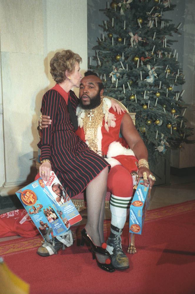 Nancy Reagan sits on Mr. T's lap while he's dressed like Santa Claus, 1983