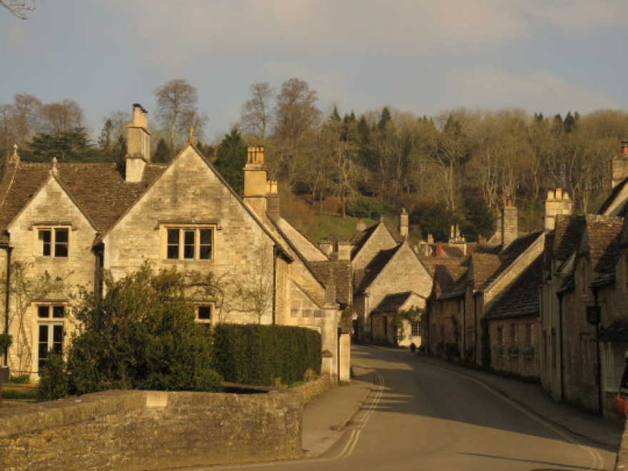 Grey stone cottages line a single street in the English village of Castle Combe