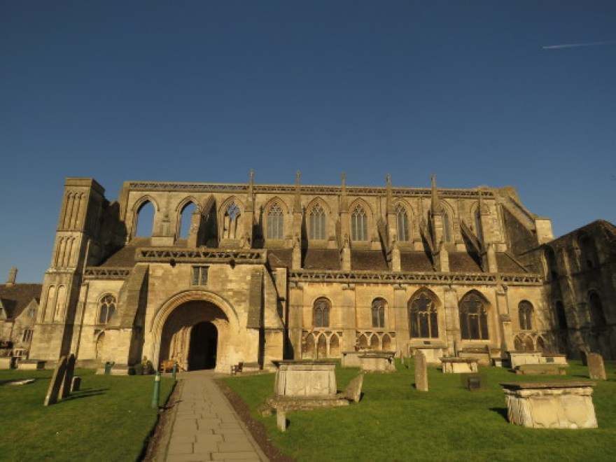 Malmesbury, England: A large stone abbey and graveyard stand out against a blue sky