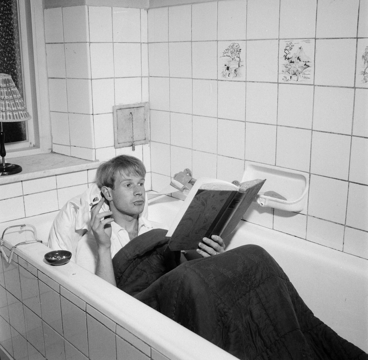 7aea13e92873 Man reading in a bath tub