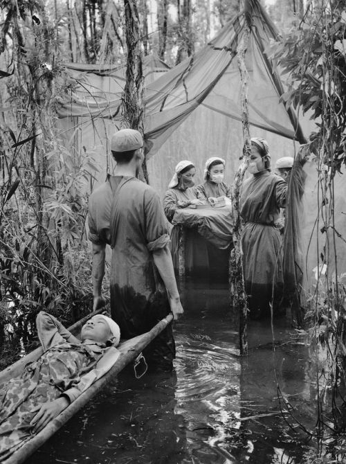 A victim of American bombing, Cambodian guerrilla Danh Son Huol, is carried to an improvised operating room in a mangrove swamp on the Ca Mau Peninsula, Vietnam, 1970. [2000 x 2677] Check this blog!