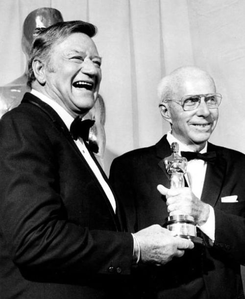 Howard Hawks receives an honorary Oscar from John Wayne
