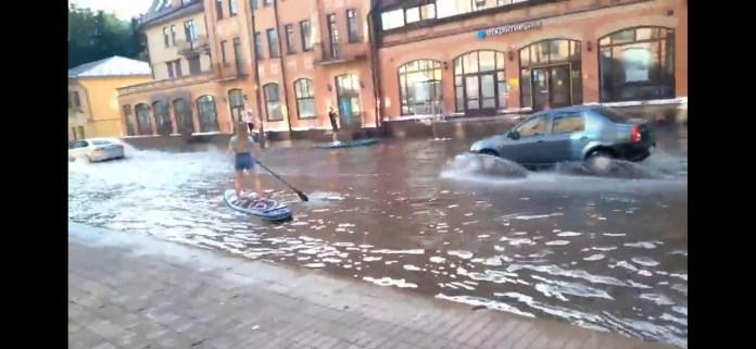 В Пскове люди катаются на досках для сапсерфинга по затопленной дороге