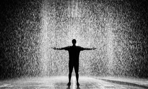 silhouette and grayscale photography of man standing under the rain