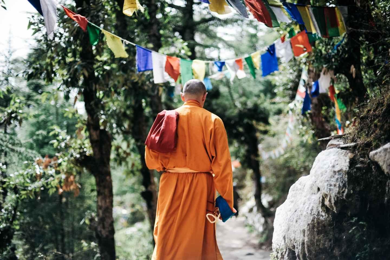 monk walking near buntings during day