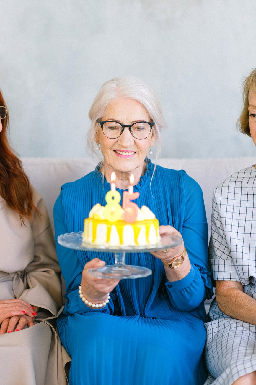 happy elderly woman with sweet birthday cake with candles