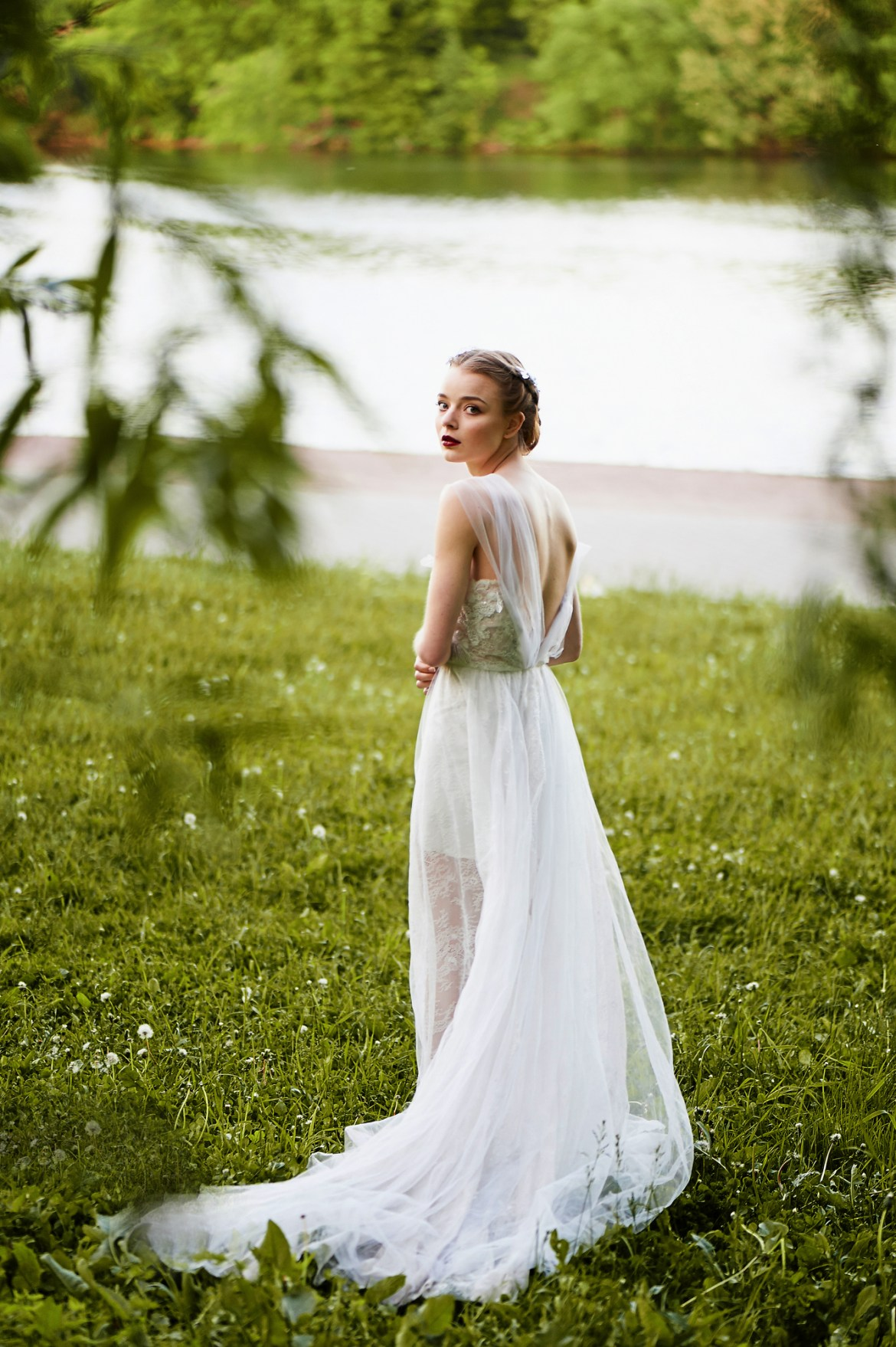 Beautiful girl in white long dress with open back. In full growth