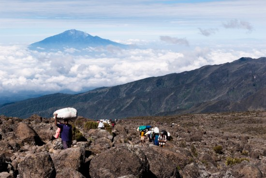 Mt Kilimanjaro, Tanzania, East Africa - February 11th 2010: 8.45am - A long trail of porters carrying provisions and equipment up along the the Machame Route up Mt Kilimanjaro having just left Shira Camp. The peak of Mount Meru breaking cloud cover in the background.