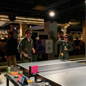 Two men in sunglasses wearing jumpsuits play ping pong