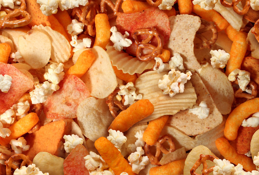 29084627 - snacks background with salty crunchy treats as potato chips and cheese flavored puffs fried or baked food as pretzels pop corn and nachos as a symbol of assorted party mix appetizer