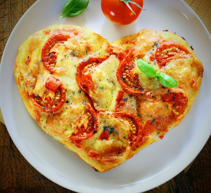 19557149 - overhead view of a romantic heart shaped italian pizza topped with a vegetarian topping of golden melted cheese and tomato on a plain white plate. more pizza at my port.