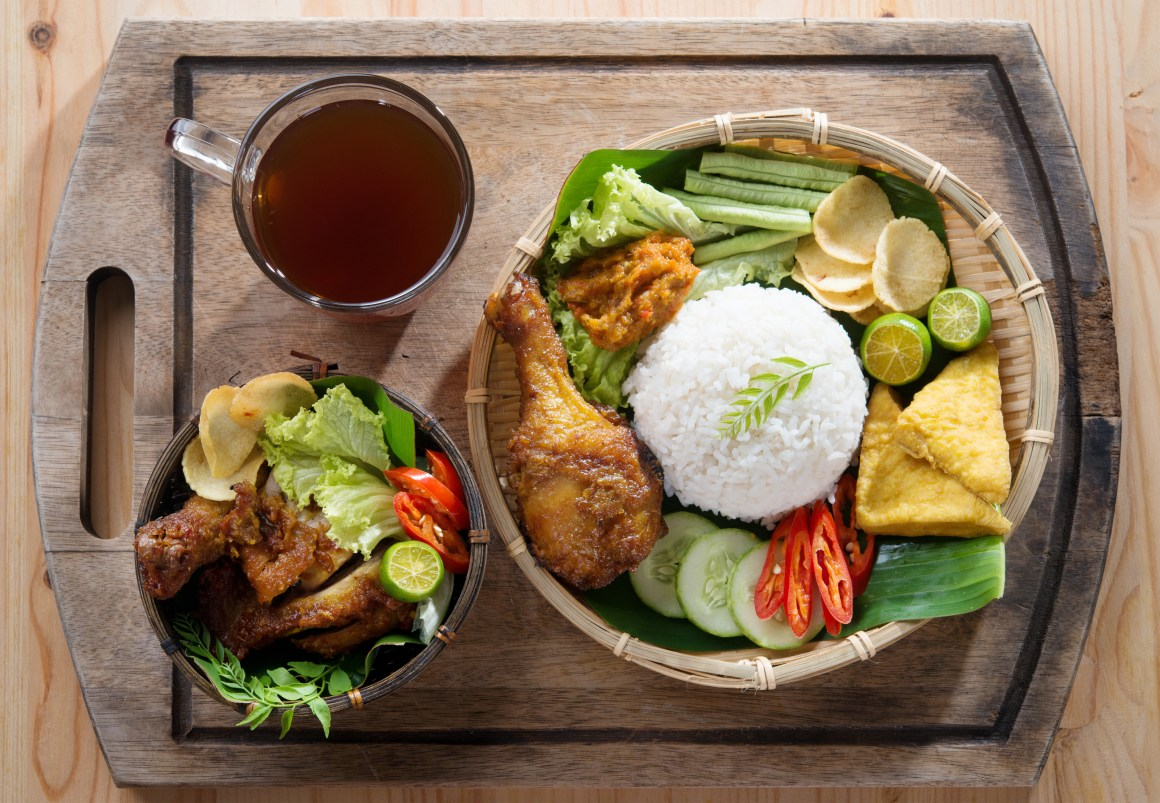 Famous traditional Indonesian food. Delicious nasi ayam penyet with sambal belacan. Fried chicken rice and tea with overhead view.