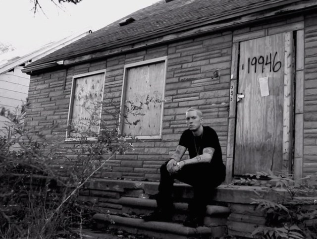 Eminem on the stoop of his former home near 8 Mile Road.