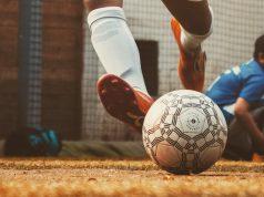 close up on soccer athlete's feet kicking ball