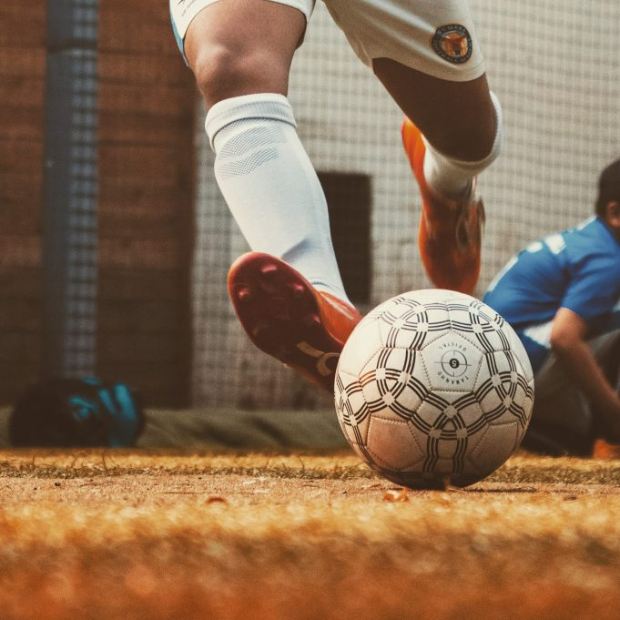 close up on soccer athlete's feet kicking ball