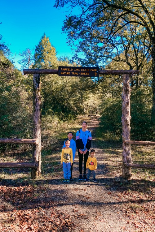 kids standing under a nature trail sign