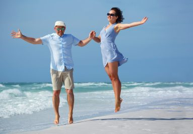 Young couple having fun at tropical beach during honeymoon, Siesta Key beach, Florida