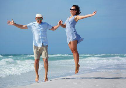Young couple having fun at tropical beach during honeymoon, Siesta Key beach, Florida