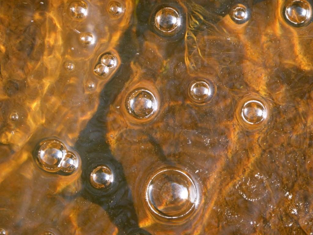 white bubbles orange ripples in stream