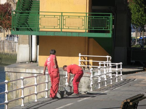 red-overalled workmen by bridge