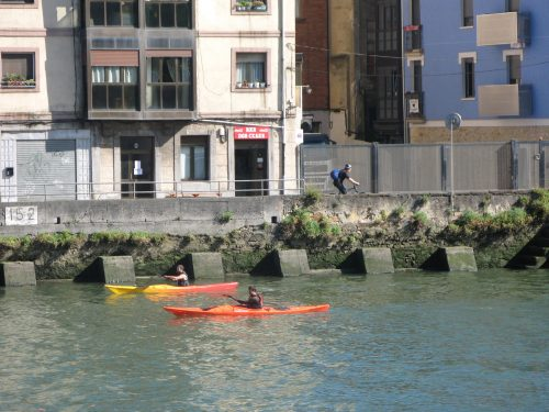 canoes and cyclist on riverbank