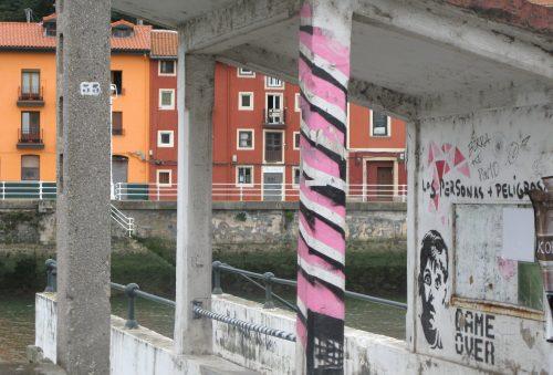 pink stripey painted bus stop pillar