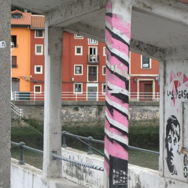 pink stripey painted bus stop pillar